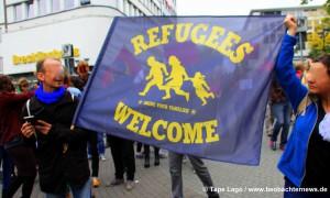 GegendemonstrantInnen heißen Flüchtlinge willkommen.